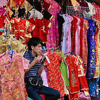 Racks of Women's Silk Clothes in Chinatown in Bangkok, Thailand <br />