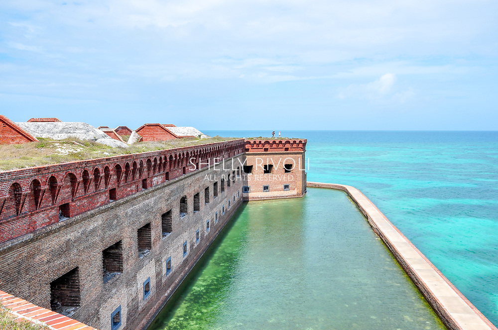 View from roof top of Fort Jefferson over moat with beautiful turquoise and clear water beside brick walls at Dry Tortugas National Park. Two tourists stand in the distance enjoying the view of the water and reef.