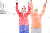 Young female friends throwing snow