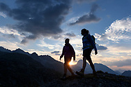 Zwei Frauen wandern in der Abendd&auml;mmerung bei den Crap Alv Laiets in der N&auml;he des Albulapasses mit Blick auf den Piz Murtel Trigd, den Piz Palpuogna und den Piz Ela, Parc Ela, Graub&uuml;nden, Schweiz<br /> <br /> Two women are hiking at dusk at the Crap Alv Laiets close to the Albula Pass with the Piz Murtel Trigd, Piz Palpuogna and the Piz Ela in sight, Parc Ela, Grisons, Switzerland