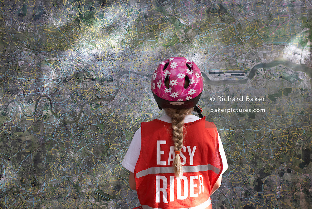 Wearing a pink-flowered safety helmet and a red reflective safety bib saying 'Easy Rider', a pig-tailed nine year-old girl cyclist examines a map of Greater London during the first traffic-free Hovis-sponsored event called 'Freewheel' when many streets in the city were closed off to cars for one Sunday, 23rd September 2007. This girl has already ridden 6 miles from the Peckham area of South London and before the day is finished, will have pedalled 10 miles more on this late-summer Sunday - starting and finishing in Peckham Rye Park. The map shows major roads in blue and minor streets in yellow with the River Thames snaking horizontally through the capital.