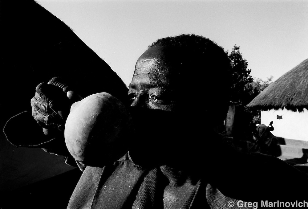IPMG0340 South Africa, Modjadji, 1989: A man drinks traditional beer from a calabash during a celebration of the first fruits ceremony as a woman sweeps the courtyard behind him in HaModjadji village in Lebowa homeland, now Limpopo Province, Oct 14, 1989. .Photograph by Greg Marinovich/South Photographs