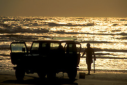 Stock photo of the silhouette of a man returning from surf fishing in the Gulf of Mexico at sunset
