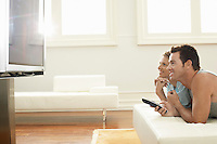 Couple lying on bed watching plasma TV together side view