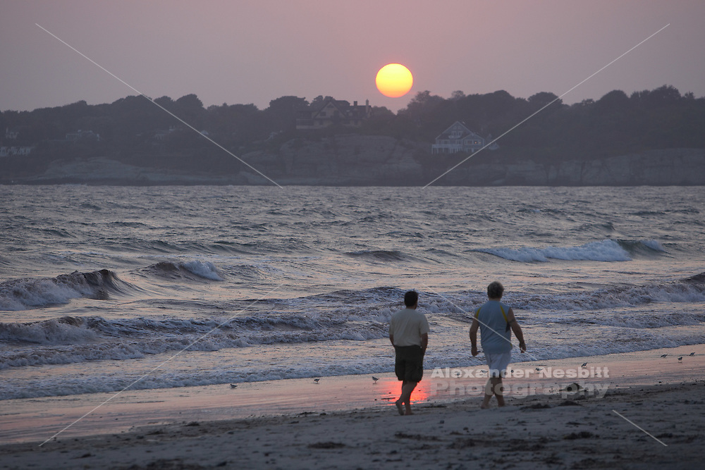 Two men stroll on second beach (Sachuest) crossing in front of sunset reflection on water - Middletown, RI 2007