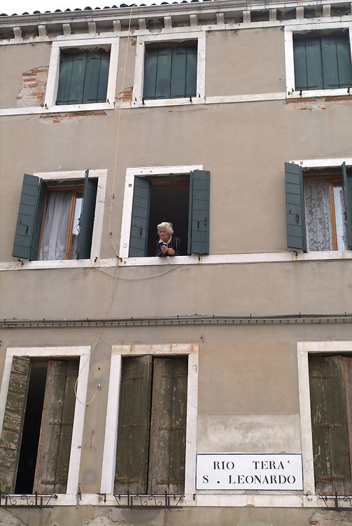 Old woman looking out window of building in Florence, Italy
