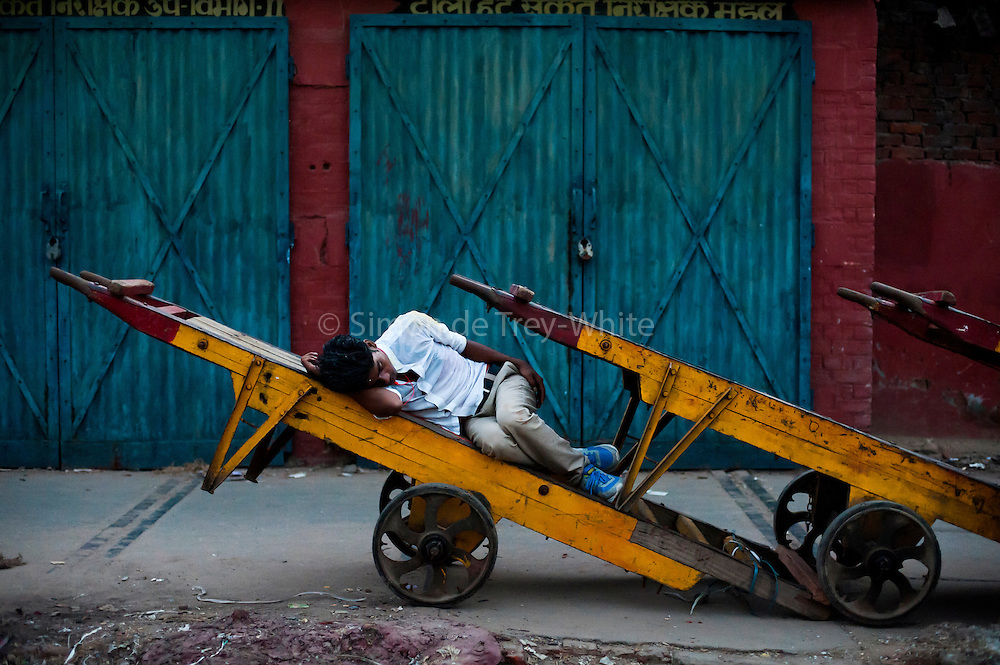 19th August 2014, New Delhi. A man sleeps on a railway cart at Nizamuddin Railway Station in New Delhi, India on the 19th August 2014<br /> <br /> Sleeping in the outdoors is common in Asia due to a warmer climate and the fact that personal privacy for sleep is not so culturally ingrained as it is in the West. New Delhi (where most of these images were taken) is a harsh city both in climate and environment and for those working long hours, often in hard manual labour, sleep and rest is something fallen into when exhaustion overwhelms, no matter the place or circumstance. Then there are the homeless, in Delhi figures for them from Government and NGO sources vary wildly from 25,000 to more than 10 times that. Others public sleepers may simply be travellers having a siesta along the way.<br />  <br /> <br /> PHOTOGRAPH BY AND COPYRIGHT OF SIMON DE TREY-WHITE, photographer in Delhi<br /> <br /> + 91 98103 99809<br /> email: simon@simondetreywhite.com