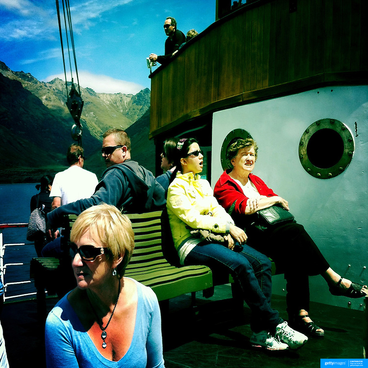 Passengers on the TSS Earnslaw, the 100 year old vintage coal fired passenger steam ship which sails on Lake Wakatipu, Queenstown, New Zealand. The popular tourist attraction is celebrating it's centenary year with celebrations planned for October 2012.  Queenstown, Central Otago, New Zealand. 29th February 2012. Photo Tim Clayton