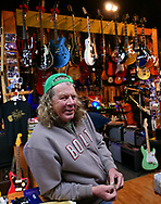Artie Niesen owner pses in front of the hundreds of guitars sold at Front Porch Music on 19th Street in downtown Bakersfield. <br />