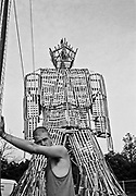 White man leans against post in front of large wickerman. Glastonbury 1994