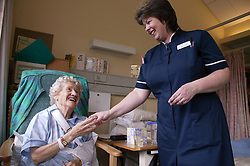 Nurse with disability administering medication to elderly patient in hospital,