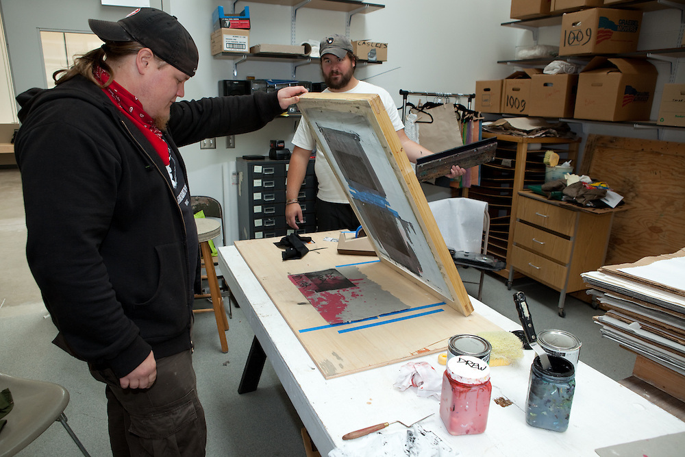 Todd Dennis (front) and Nathan Toth working at the sikscreenst sation. Combat Paper participants in a workshop in the Paper Lab in the Department of Art at the University of Wisconsin-Madison.