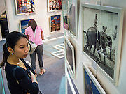 19 JULY 2013 - BANGKOK, THAILAND:   A Thai woman looks at photos hanging at a photo exhibit about Thai-US relations in CentralWorld in Bangkok. The US Embassy in Bangkok sponsored the photo exhibit, which celebrates 180 years of US-Thai diplomatic relations. There are 180 photos hanging in the show, 90 by American photographers in Thailand and 90 by Thai photographers in the United States. The show, which opened July 19, is hanging in CentralWorld, a large mall in Bangkok, and is touring Thailand when it concludes its Bangkok run on July 21.   PHOTO BY JACK KURTZ