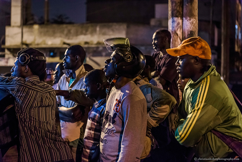 Some audience watches a wrestling fight on TV on the street in Dakar on April 4, 2015, the independance day of Senegal.