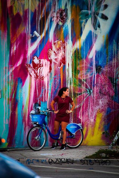 Woman on bicycle beside the painted wall of the Wynwood Diner