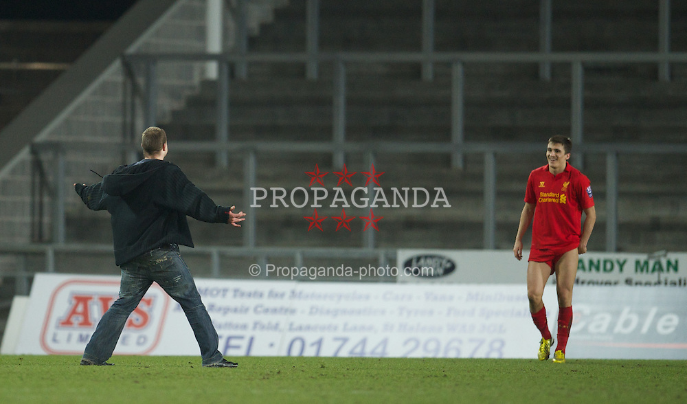 ST HELENS, ENGLAND - Monday, February 25, 2013: A Manchester United supporter runs onto the pitch to confront Liverpool's Adam Morgan during the Premier League Academy match at Langtree Park. (Pic by David Rawcliffe/Propaganda)