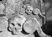 Gravestone skulls staring with dead empty eye sockets, Headington Church, Oxford, UK 2004