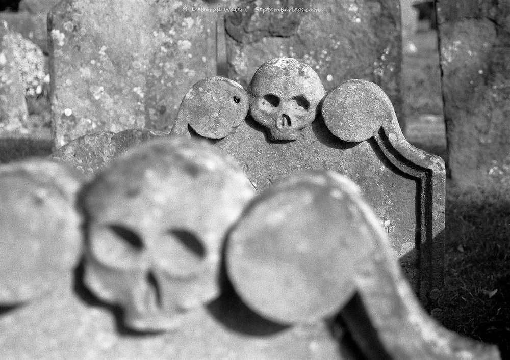 Gravestone skulls staring with dead empty eye sockets, Headington Church, Oxford, UK 2004