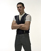Young man wearing mod style clothing posing with arms crossed.