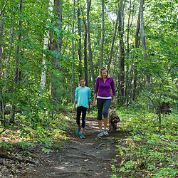 A woman and her daughter walk on a forest trail at Barker's Farm in Stratham, New Hampshire.
