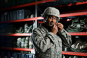 A U.S. Air Force member tries on a helmet during the deployment issue line...All Airman who are preparing to deploy must go through the mobility line. There are Airman in charge of keeping supply levels up, inventorying and issuing the gear. Certain military kits are contained in olive drab colored duffle bags and grouped by contents.