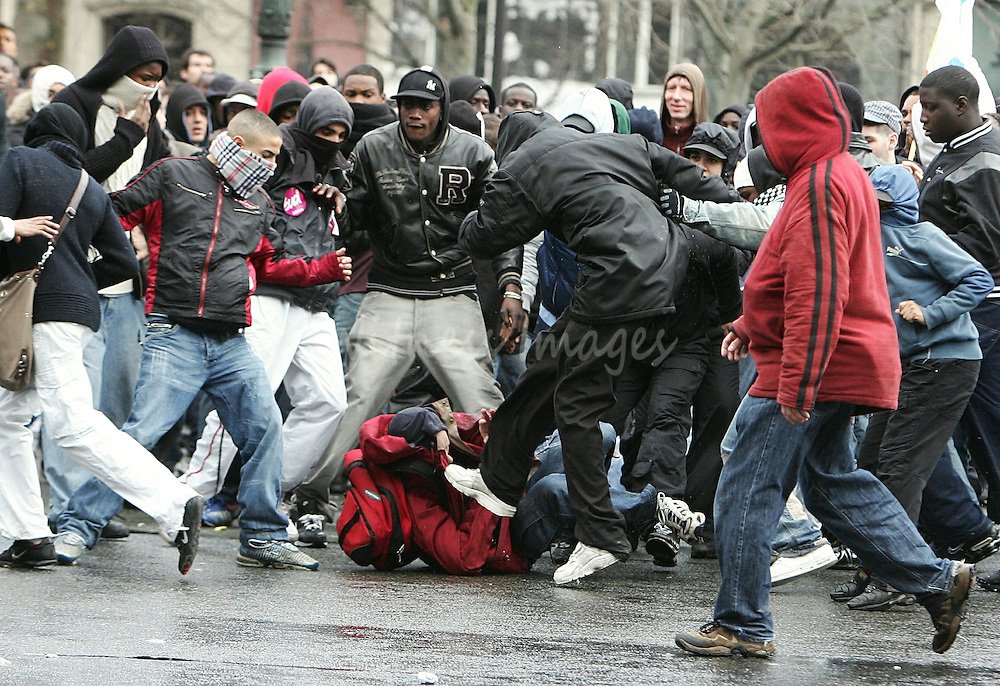 A French student is attacked by a gang of hooded youths from poor suburbs during a nationwide protest demanding the government to scrap a youth jobs law during a demonstration in Place de la Republique in Paris March 28, 2006. Students and unions in France stepped up protests against the First Employment Contract (CPE) law, an open-ended contract for under 26-year-olds that can be terminated within the first two years without justification.  REUTERS/Thierry Roge