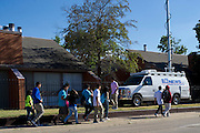 Students walk home past the media and Ivy Apartments where Thomas E. Duncan, the first confirmed Ebola virus patient in the United States, was staying with family in Dallas, Texas on October 3, 2014. Duncan is now being treated at Texas Health Presbyterian Hospital Dallas while members of his family have been isolated in the apartment. (Cooper Neill for The New York Times)