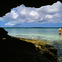 Coral reef cave and a girl in swimsuit wading in bay waters of the northern Bahamas.  Harbor Island, Bahamas.