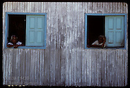 Two aged women gaze from window frames of their home with weary expressions in Eirunepe, AM. Brazil