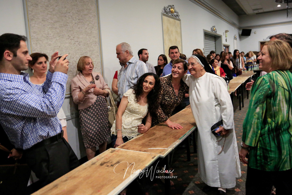 A nun visiting from Iraq is surrounded by parishioners during a reception for newly ordained priests at St. Peter Chaldean Catholic Cathedral in El Cajon, Calif., Aug. 14, 2015. (Nancy Wiechec for ONE magazine)