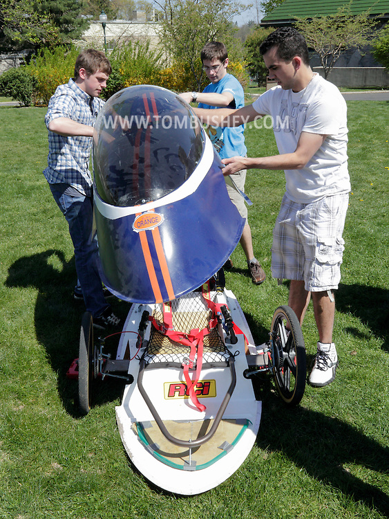 Middletown, New York - SUNY Orange students remove the top from a battery powered electric vehicle during an Earth Day celebration on the campus green on April 19, 2012.