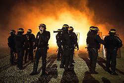 """© Licensed to London News Pictures . 23/10/2016 . Calais , France . Riot police at the Calais migrant camp known as """" The Jungle """" , in Northern France , on the evening before the start of the eviction and destruction of the camp . Photo credit: Joel Goodman/LNP"""