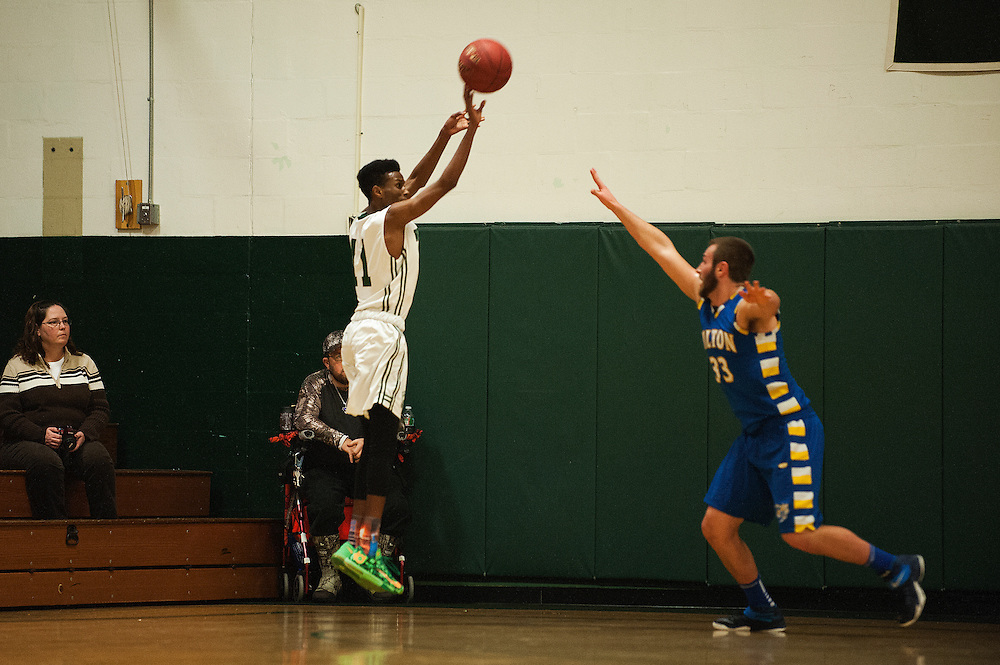 Winooski's Jibril Abdullahi (11) shoots a three pointer during the boys basketball game between the Milton Yellowjackets and the Winooski Spartans at Winooski High School on Tuesday evening December 29, 2015 in Winooski. (BRIAN JENKINS/for the FREE PRESS)