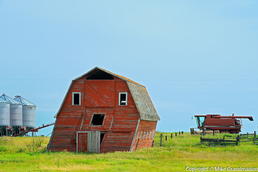 Leaning barn and combine<br /> Loreburn<br /> Saskatchewan<br /> Canada