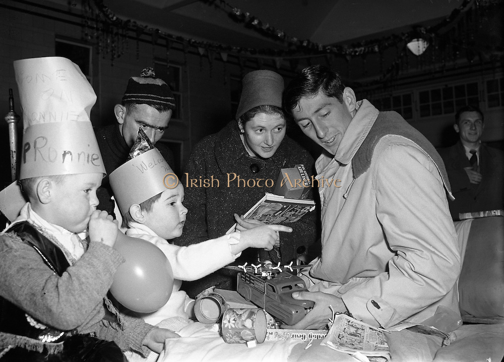 Ronnie Delaney at Cappagh Hospital.22/12/1956..Ronald Michael Delany (born 6 March 1935), better known as Ron or Ronnie is a former Irish athlete, who specialised in middle distance running...Born in Arklow, Delany moved with his family to Dublin when he was 6. His father had got a job in Jacobs Biscuit Factory and there Delany went to Catholic University School...Delany studied in the United States at Villanova University, where he was coached by the well-known track coach Jumbo Elliott. His first achievement of note was reaching the final of the 800m at the 1954 European Championships in Bern...In 1956, he became the seventh runner to join the club of Four-minute milers, but nonetheless struggled to make the Irish team for the 1956 Summer Olympics held in Melbourne...Delany qualified for the Olympic 1500 m final, in which home runner John Landy was the big favourite. Delany kept close to Landy until the final lap, when he started a crushing final sprint, winning the race in a new Olympic Record.[3] Delany thereby became the first Irishman to win an Olympic title in athletics since Bob Tisdall in 1932...Delany won the Bronze medal at the 1958 European Championships at 1500m..Delany went on to represent Ireland once again at the 1960 Summer Olympics held in Rome, this time in the 800 metres. He finished 6th in his quarter-final...He remained the last Olympics champion of Ireland for 36 years, until Michael Carruth won the gold medal in boxing at the 1992 Olympics in Barcelona...Delany continued his running career in North America, winning four successive AAU titles in the mile, adding to his total of four Irish national titles, and three NCAA titles. He was next to unbeatable on indoor tracks over that period, which included a 40-race winning streak. He broke the World Indoor Mile Record on three occasions.