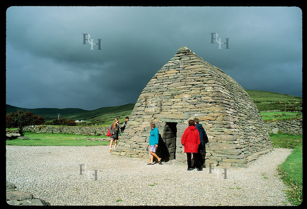 Storm hovers over tourists @ Gallarus Oratory (7th-c), a pristine early Christian church; Dingle. Ireland