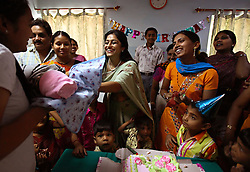 Dr. Nayna Patel, holding baby, Kaival Hospital director, holds a birthday party for a still-unnamed newborn on his last day at the clinic before going home with his biological parents in Anand, India on April 12, 2007. The couple, who wished not to be named, is from Hyderabad in southern India and had been trying for a baby for 15 years and suffered six miscarriages. (Directly left of Dr. Patel) The surrogate Daxa (no surname), 28, agreed to be a surrogate so she could build a better house for her family. The party was also meant to celebrate the first birthday of the first surrogate baby at the clinic. The surrogate of that baby is Pushpa Pandya, 27, standing to the right of Dr. Patel.
