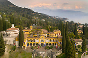 La Prioria, home of Gabriele D'Annunzio, 1863-1938, Italian writer, soldier and fascist, aerial view, at Vittoriale degli italiani, or The Shrine of Italian Victories, his estate and museums at Gardone Riviera, Lake Garda, Brescia, Lombardy, Italy. The house was originally the Villa Cargnacco, which was rebuilt by Gian Carlo Maroni from 1922 and developed until 1955. The estate consists of the Prioria, where d'Annunzio lived 1922-38, an amphitheatre, the protected cruiser Puglia, the MAS vessel used by D'Annunzio in 1918 and a mausoleum. It is part of the Grandi Giardini Italiani. Picture by Manuel Cohen