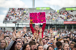 "© Licensed to London News Pictures . 04/06/2017 . Manchester , UK . A woman in the audience holds up a "" One Love One heart and One soul "" poster . The One Love Manchester benefit concert for victims of the Manchester Arena terrorist attack , at the Emirates Old Trafford Cricket Stadium . Ariana Grande, Justin Bieber, Coldplay, Katy Perry, Miley Cyrus, Pharrell Williams, Usher, Take That, Robbie Williams, Black Eyed Peas and Niall Horan are amongst the performers. Photo credit : Joel Goodman/LNP"