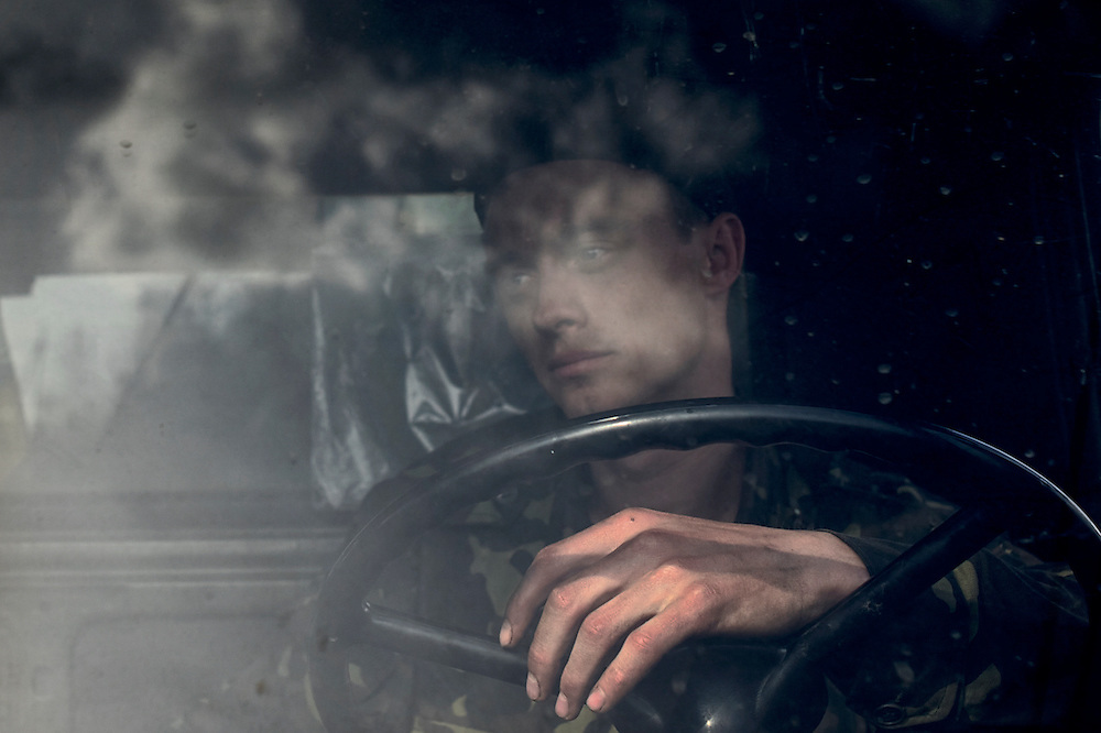 An Ukrainian soldier sits inside a military vehicle blocked by a group of pro-Russia activists preventing an army convoy to pass in the eastern Ukrainian city of Kramatorsk in the Donetsk region.