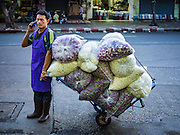30 JUNE 2016 - BANGKOK, THAILAND: A vendor wheels away what's left of his daily supply of flowers in the sidewalk market at Pak Khlong Talat. Sidewalk vendors around Pak Khlong Talat, Bangkok's famous flower market, face eviction if they reopen on July 1. As a part of the military government sponsored initiative to clean up Bangkok, city officials have been trying to shut down the sidewalk vendors around the flower market. The vendors were supposed to be gone by the end of March, but city officials relented at the last minute with a compromise allowing vendors to stay until June 30. When vendors dismantled their booths after business on June 30, they weren't sure if they will be allowed to reopen July 1. Some vendors have moved to new locations approved by the government but many have not because they can't afford the higher rents in the new locations.     PHOTO BY JACK KURTZ
