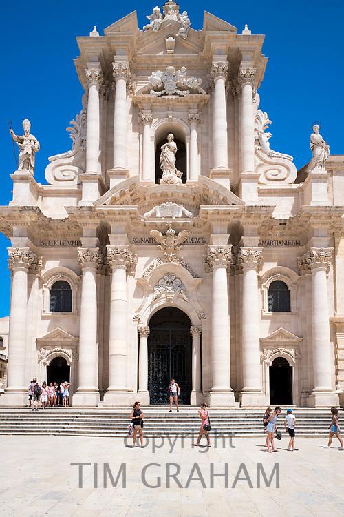 Tourists visiting Duomo di Siracusa cathedral Temple of Minerva - Tempio di Minerva - front elevation in Piazza Duomo in Ortigia, Sicily, Italy
