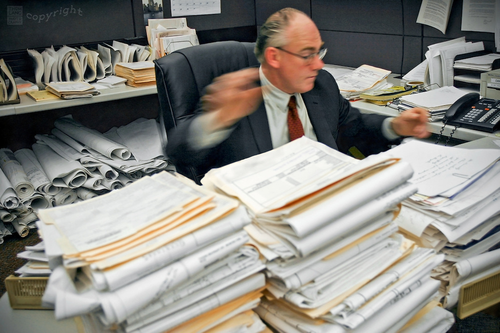 An overworked office worker is surrounded by stacks of papers.