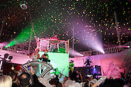 The DJ Mowgli spins tunes from the top of a raised platform, as dancers perform and a longtime tradition of confettii at midnight continues during Masquerage 2012 in the Roundhouse at the Montgomery County Fairgrounds in Dayton, Saturday, October 20, 2012..