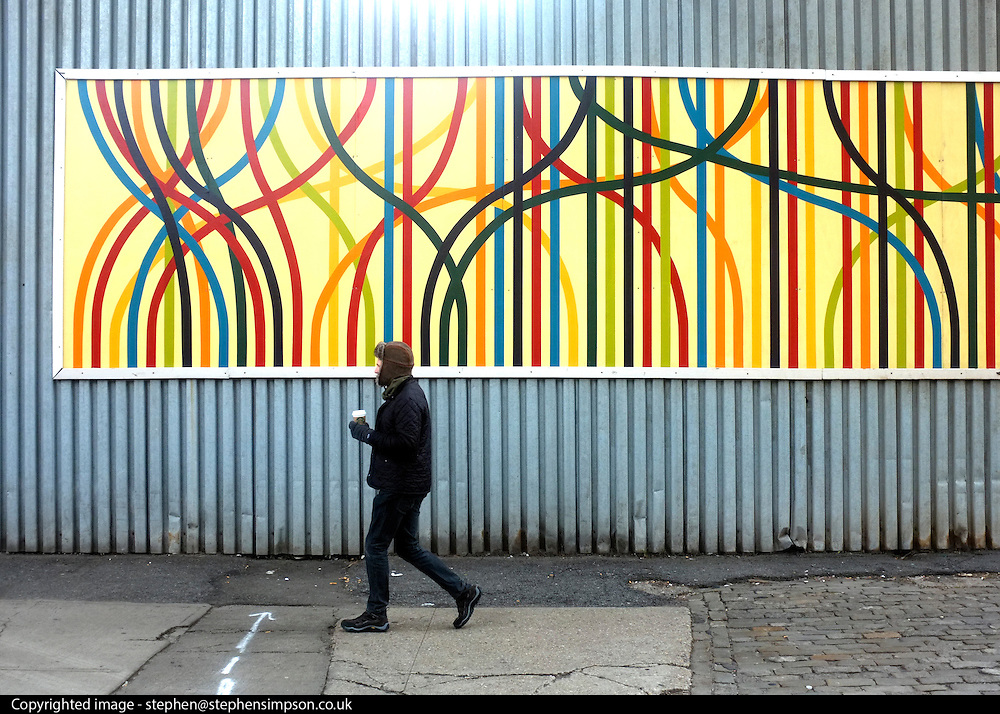 © Licensed to London News Pictures. 04/01/2013. New York City, USA . A man walks past a billboard. Photo credit : Stephen Simpson/LNP