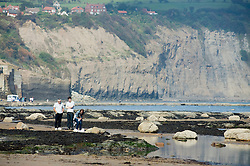tourist on the shore line Robin Hoods Bay north Yorkshire.September 2010 .Images © Paul David Drabble