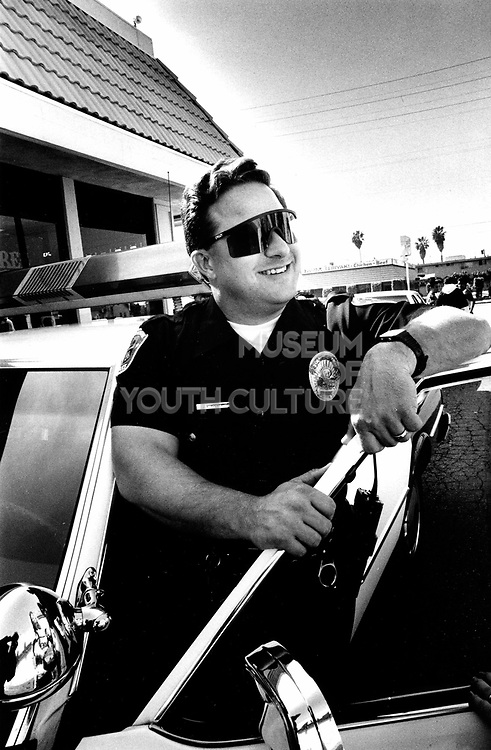 An LAPD officer posing by his squad car in his shades, LA, USA, 1990's