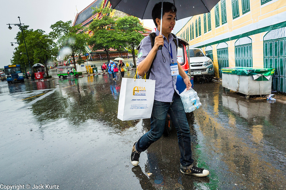 23 SEPTEMBER 2013 - BANGKOK, THAILAND:  A tour guide carries bottled water through a rain storm in Bangkok. More than a quarter of the provinces in Thailand are reporting some flooding as heavy rainy season storms continue in central Thailand. Rain is expected to continue through this week, raising the possibility of serious flooding throughout the country. More than 600,000 Thais have been impacted by the flooding so far this year. Flooding in 2011 killed more than 800 people and cut economic growth for the year to just .10 percent.    PHOTO BY JACK KURTZ