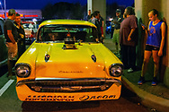 Bellmore, New York, USA. 7th August 2015. Groups of people are at yellow 1957 Chevrolet muscle car, with a blower (supercharger air compressor) sticking out through hole in hood, and American Dream written under the front grill, is parked under the elevated train tracks at the Friday Night Car Show held at the Bellmore Long Island Railroad Station Parking Lot. Hundreds of classic, antique, and custom cars were on view at the free weekly show, sponsored by the Chamber of Commerce of the Bellmores.