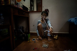An addict is smoking Ice in her room in Phnom Penh, Cambodia. <br />